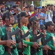 "In formation. Fighters of the NPA Guerrilla Front 16 present arms as they sing ""Ang Internasyunal."""